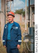 Мужчина инженер в синей спецовке и каске на электрической подстанции. Стоковое фото, фотограф Станислав Илюк / Фотобанк Лори