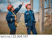 Мужчина и женщина инженеры в синих спецовках и касках на электрической подстанции. Стоковое фото, фотограф Станислав Илюк / Фотобанк Лори