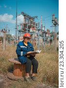 Женщина инженер в спецовке и каске сидит на фоне электрической подстанции. Стоковое фото, фотограф Станислав Илюк / Фотобанк Лори