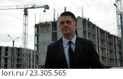 Купить «Бизнесмен с планшетом возле строительства нового здания», видеоролик № 23305565, снято 18 июля 2016 г. (c) Алексей Собченко / Фотобанк Лори