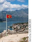 Флаг Черногории на стенах крепости St. John (San Giovanni) на фоне Которского залива и города Котор, Черногория (2016 год). Стоковое фото, фотограф Кекяляйнен Андрей / Фотобанк Лори