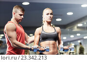 Купить «young couple with dumbbells flexing muscles in gym», фото № 23342213, снято 19 апреля 2015 г. (c) Syda Productions / Фотобанк Лори