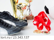 Купить «close up of football boots, cups and medals», фото № 23343137, снято 17 июня 2016 г. (c) Syda Productions / Фотобанк Лори