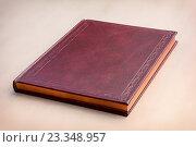 Купить «Красная книга в твердом переплете лежит на светлом фоне», фото № 23348957, снято 27 мая 2019 г. (c) Андрей С / Фотобанк Лори