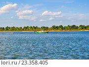 Моторная лодка плывет по реке на фоне леса и голубого неба. Стоковое фото, фотограф Юра Добро / Фотобанк Лори