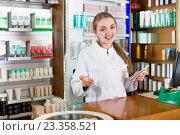 Купить «Cheerful young female pharmacist posing», фото № 23358521, снято 20 апреля 2019 г. (c) Яков Филимонов / Фотобанк Лори