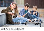 Купить «Three teenagers with phones outdoors», фото № 23358589, снято 19 июня 2019 г. (c) Яков Филимонов / Фотобанк Лори