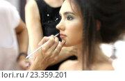 Купить «Визажист делает модели красивый макияж, парикмахер делает прическу», видеоролик № 23359201, снято 5 августа 2016 г. (c) Константин Шишкин / Фотобанк Лори