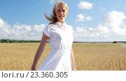 Купить «smiling young woman in white dress on cereal field», видеоролик № 23360305, снято 3 августа 2016 г. (c) Syda Productions / Фотобанк Лори