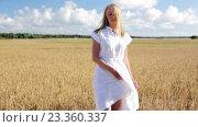 Купить «smiling young woman in white dress on cereal field», видеоролик № 23360337, снято 3 августа 2016 г. (c) Syda Productions / Фотобанк Лори