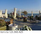 Купить «Кафе у моря, цветы в кадках и белые зонтики, люди отдыхают», фото № 23360425, снято 7 июня 2016 г. (c) DiS / Фотобанк Лори