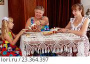 Купить «Девочка с мамой и бабушкой пьют чай за столом», фото № 23364397, снято 13 июля 2016 г. (c) Сергей Колесников / Фотобанк Лори
