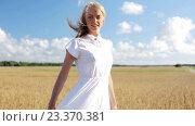 Купить «smiling young woman in white dress on cereal field», видеоролик № 23370381, снято 6 августа 2016 г. (c) Syda Productions / Фотобанк Лори