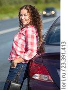 Купить «Девушка в красной клетчатой рубашке стоит у машины на дороге», фото № 23391413, снято 12 августа 2016 г. (c) Кекяляйнен Андрей / Фотобанк Лори