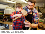 Купить «father and son with chisel working at workshop», фото № 23402509, снято 14 мая 2016 г. (c) Syda Productions / Фотобанк Лори