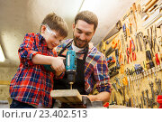 Купить «father and son with drill working at workshop», фото № 23402513, снято 14 мая 2016 г. (c) Syda Productions / Фотобанк Лори