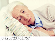sad senior woman lying on pillow at home. Стоковое фото, фотограф Syda Productions / Фотобанк Лори