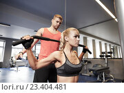 Купить «man and woman flexing muscles on gym machine», фото № 23404481, снято 19 апреля 2015 г. (c) Syda Productions / Фотобанк Лори