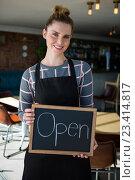 Купить «Portrait of waitress showing slate with open sign», фото № 23414817, снято 6 июня 2016 г. (c) Wavebreak Media / Фотобанк Лори