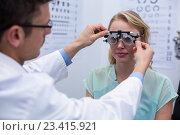 Купить «Optometrist examining female patient with phoropter», фото № 23415921, снято 19 июня 2016 г. (c) Wavebreak Media / Фотобанк Лори