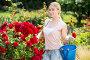 Blond woman taking care of red rose bushes, фото № 23421977, снято 23 августа 2016 г. (c) Яков Филимонов / Фотобанк Лори