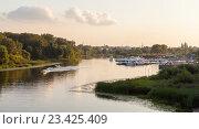 Купить «Моторная лодка плывет по реке на закате, пирс и город на заднем плане», фото № 23425409, снято 21 августа 2016 г. (c) Илья Бесхлебный / Фотобанк Лори