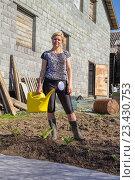 Купить «Женщина с желтой лейкой на дачном участке», фото № 23430753, снято 12 мая 2013 г. (c) Евгений Ткачёв / Фотобанк Лори