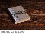 Старая книга и старинные круглые очки для чтения на деревянном фоне. Стоковое фото, фотограф Юра Добро / Фотобанк Лори