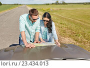 Купить «happy man and woman with road map on car hood», фото № 23434013, снято 12 июня 2016 г. (c) Syda Productions / Фотобанк Лори