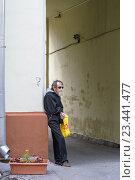 Москва, Россия - 7 июля 2016: Пожилой бездомный мужчина стоит и просит милостыню в подворотне. Редакционное фото, фотограф Игорь Травкин / Фотобанк Лори