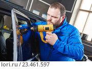 Купить «car tinting. Automobile mechanic technician applying foil», фото № 23461597, снято 14 апреля 2016 г. (c) Дмитрий Калиновский / Фотобанк Лори