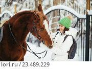 Купить «Девушка с конем стоит в зимнем парке. Фокус на морде животного», фото № 23489229, снято 19 декабря 2015 г. (c) Рустам Шигапов / Фотобанк Лори