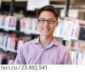 Купить «Happy male student holding books at the library», фото № 23492541, снято 25 ноября 2014 г. (c) Sergey Nivens / Фотобанк Лори