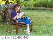 Купить «Девочка в кресле на даче листает учебник», фото № 23495445, снято 4 сентября 2016 г. (c) Наталья Гармашева / Фотобанк Лори