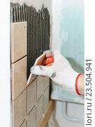 Рабочий кладет плитку на стену в кухне. Стоковое фото, фотограф Владимир Ворона / Фотобанк Лори