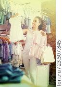 Купить «Cheerful woman customer holding baby dress», фото № 23507845, снято 24 февраля 2019 г. (c) Яков Филимонов / Фотобанк Лори