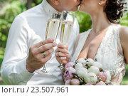 Купить «Бокалы с шампанским в руках на фоне поцелуя жениха и невесты», эксклюзивное фото № 23507961, снято 16 июля 2016 г. (c) Игорь Низов / Фотобанк Лори