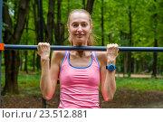 Купить «Стройная девушка подтягивается на турнике в парке», фото № 23512881, снято 26 августа 2016 г. (c) Антон Гвоздиков / Фотобанк Лори