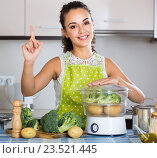 Cheerful girl cooking vegetables at steamer. Стоковое фото, фотограф Яков Филимонов / Фотобанк Лори
