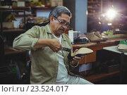 Купить «Shoemaker repairing a high heel», фото № 23524017, снято 12 июня 2016 г. (c) Wavebreak Media / Фотобанк Лори