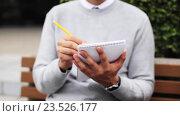 Купить «man with notebook or diary writing on city street», видеоролик № 23526177, снято 26 августа 2016 г. (c) Syda Productions / Фотобанк Лори