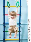 Купить «child hanging on gymnastic rings», фото № 23537169, снято 7 февраля 2015 г. (c) Оксана Кузьмина / Фотобанк Лори