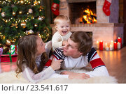 Happy parents and child have a fun near Christmas tree at home. Father, mother, son celebrating New Year together. Стоковое фото, фотограф Оксана Кузьмина / Фотобанк Лори