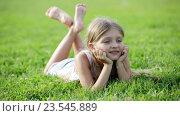small girl lying on green grass in park. Стоковое видео, видеограф Яков Филимонов / Фотобанк Лори