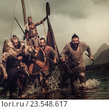 Купить «Mad vikings warriors in the attack, running along the shore with Drakkar on the background.», фото № 23548617, снято 29 августа 2016 г. (c) Andrejs Pidjass / Фотобанк Лори