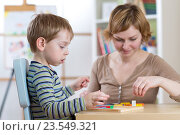 Купить «Child boy playing with education toys at the table in kindergarten», фото № 23549321, снято 23 февраля 2016 г. (c) Оксана Кузьмина / Фотобанк Лори