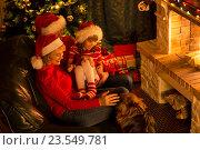 Купить «Happy family in red hats with cute dog sitting at Christmas tree near fireplace», фото № 23549781, снято 19 ноября 2015 г. (c) Оксана Кузьмина / Фотобанк Лори
