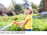Купить «Happy girl pours water from a hose in garden», фото № 23549821, снято 3 сентября 2015 г. (c) Оксана Кузьмина / Фотобанк Лори