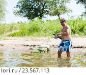 Купить «Рыбак со спиннингом ловит рыбу в реке», эксклюзивное фото № 23567113, снято 9 августа 2016 г. (c) Игорь Низов / Фотобанк Лори