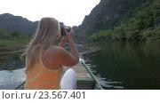 Купить «In Trang an bai in Hanoi, Vietnam girl on the boat in river photographing on SLR camera», видеоролик № 23567401, снято 6 мая 2016 г. (c) Данил Руденко / Фотобанк Лори